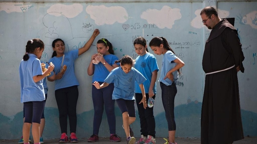 FILE - In this Tuesday, May 26, 2015 file photo, Arab Israeli Christian school children play at the Terra Santa School in the mixed Jewish-Arab city of Ramle, Israel. About 2,500 striking demonstrators gathered Sunday, Sept. 6, 2015, outside the prime minister's office in Jerusalem, police said, to protest against the slashing of funds for Christian schools. Christian school administrators accuse Israel of cutting their funding as a tactic to pressure them to join the Israeli public school system _ a move they say would interfere with the schools' Christian values and high academic achievements. (AP Photo/Oded Balilty, File)