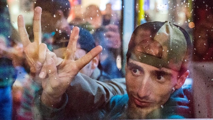 Refugees show the victory sign behind a bus window as they leave the train station in Saalfeld, central Germany, Saturday, Sept. 5, 2015. Hundreds of refugees arrived to Saalfeld in a train from Munich to be transported by busses to an accomodation centre. (AP Photo/Jens Meyer)