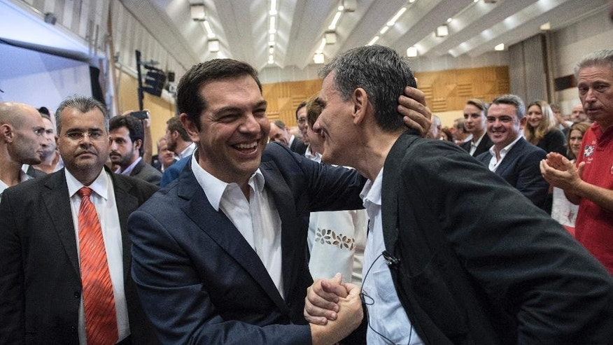 Alexis Tsipras, left, leader of left-wing Syriza party and former prime minister, greets former Finance minister Euclid Tsakalotos, before delivering a pre-election speech at the 80th Thessaloniki International Trade Fair (TIF) in the northern Greek port city of Thessaloniki, Sunday, Sept. 6, 2015. Greece heads to general parliamentary elections on Sept. 20, highlighting Greece's need to keep its European course.  (AP Photo/Giannis Papanikos)
