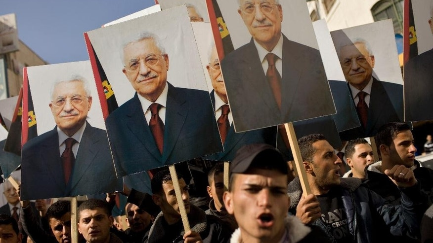 FILE - In this Jan. 28, 2011 file photo, Palestinian Fatah supporters hold placards of Palestinian President Mahmoud Abbas during a rally in support of Abbas, in the West Bank city of  Ramallah. With paths to Palestinian statehood blocked, President Mahmoud Abbas is warning he's fast-tracking his retirement and hinting he will announce dramatic policy changes at the United Nations General Assembly on Sept. 30, 2015 including a more-confrontational relationship with Israel's right-wing government. (AP Photos/Bernat Armangue, File)