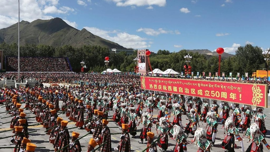 "In this photo released by China's Xinhua News Agency, phalanxes attend a grand ceremony marking the 50th anniversary of the founding of the Tibet Autonomous Region at the square of the Potala Palace in Lhasa, capital of southwest China's Tibet Autonomous Region, Tuesday, Sept. 8, 2015. Schoolchildren waved flags and paramilitary troops marched in full battle dress as the Chinese government on Tuesday staged a mass spectacle marking 50 years since Tibet's establishment as an ethnic autonomous region firmly under the control of Beijing. The banner reads: ""Celebration for the 50th anniversary of the founding of the Tibet Autonomous Region."" (Pang Xinglei/Xinhua via AP) NO SALES"