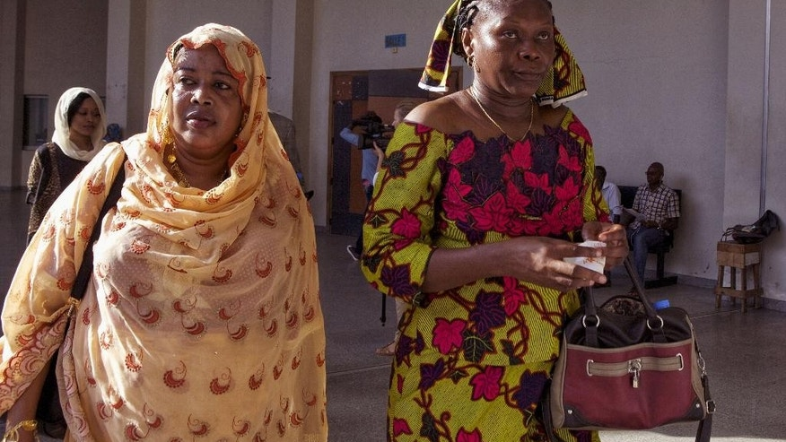 Haoua Brahim, left, and Rachel Mouaba, right, victims of former Chadian dictator Hissene Habre arrive to testify during his trail in Dakar, Senegal, Monday, Sept. 7, 2015. Security officers dragged former Chadian dictator Hissene Habre into the courtroom Monday after he refused to take part in his trial on war crimes charges, and some of his supporters had to be removed after they charged to the front of the court. (AP Photo/Jane Hahn)
