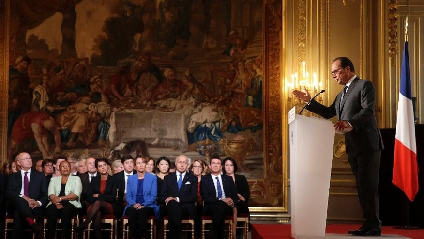 Cabinet members listen to French President Francois Hollande, right, during his press conference at the Elysee Palace in Paris, France, Monday Sept.7, 2015. France will send reconnaissance flights over Syria beginning Tuesday to help plan airstrikes in the fight against the Islamic State group, the president said.  (Philippe Wojazer, Pool via AP)