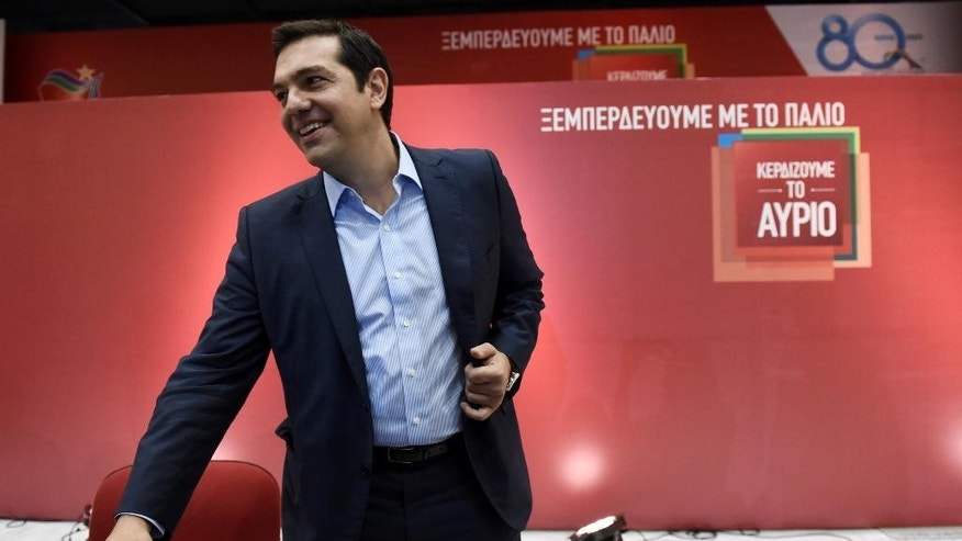 """The leader of the left-wing Syriza party and former Greek Prime Minister Alexis Tsipras arrives for a news conference at the Vellidio Convention Center in the northern Greek city of Thessaloniki, Monday, Sept. 7, 2015. Tsipras said Sunday the upcoming national election, Sept. 20, is a battle between his """"honorable"""" government of the past seven months and """"the dark period of corruption, cronyism and power networks"""" that prevailed in previous decades. The banner on the background reads: """"We get rid of the past"""" and """"We Win Tomorrow"""". (AP Photo/Giannis Papanikos)"""