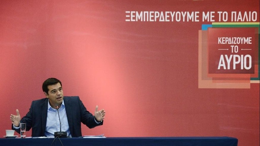 """The leader of the left-wing Syriza party and former Greek Prime Minister Alexis Tsipras answers a question during a news conference at the Vellidio Convention Center in the northern Greek city of Thessaloniki, Monday, Sept. 7, 2015. Tsipras said Sunday the upcoming national election, Sept. 20, is a battle between his """"honorable"""" government of the past seven months and """"the dark period of corruption, cronyism and power networks"""" that prevailed in previous decades. The banner on the background reads: """"We get rid of the past"""" and """"We Win Tomorrow"""". (AP Photo/Giannis Papanikos)"""