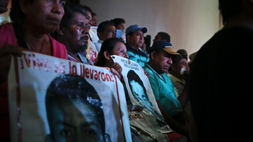 Parents of the 43 teachers' college students hold up images of their missing sons as they listen in to a conference in Mexico City, Sunday, Sept. 5, 2015. An independent report presented Sunday dismantled the Mexican government's investigation into last year's disappearance of the 43 students, saying the prosecutor's contention that they were incinerated in a giant pyre never happened and fueling the anger of parents who still don't know what happened to their sons. (AP Photo/Emilio Espejel)