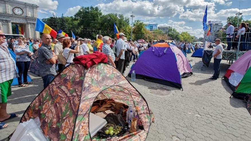 People stand next to protester's tents in downtown Chisinau, Moldova, Monday, Sept. 7, 2015. Tens of thousands of people have protested in Moldova's capital, Sunday, calling on the government to properly investigate the up to $1.5 billion that disappeared from three banks last year.(AP Photo/Vitalie Plotnic)