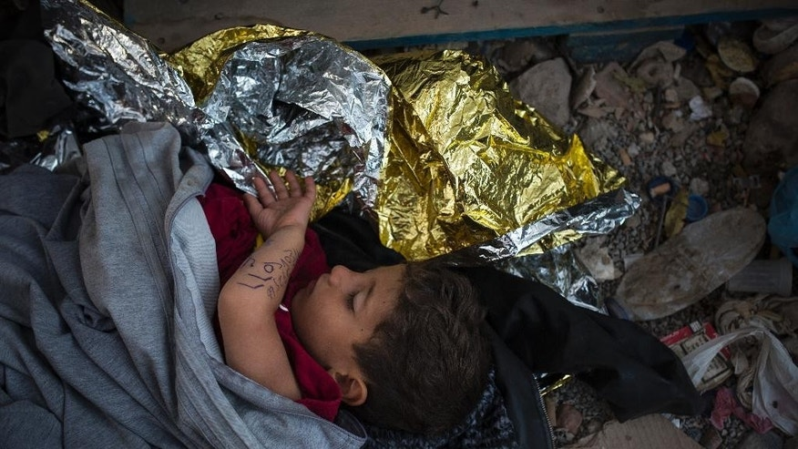 A Syrian boy, his parents phone number written on his arm, sleeps at the port of Mytilene, on the Greek island of Lesbos, early Sunday, Sept. 6, 2015. (AP Photo/Santi Palacios)