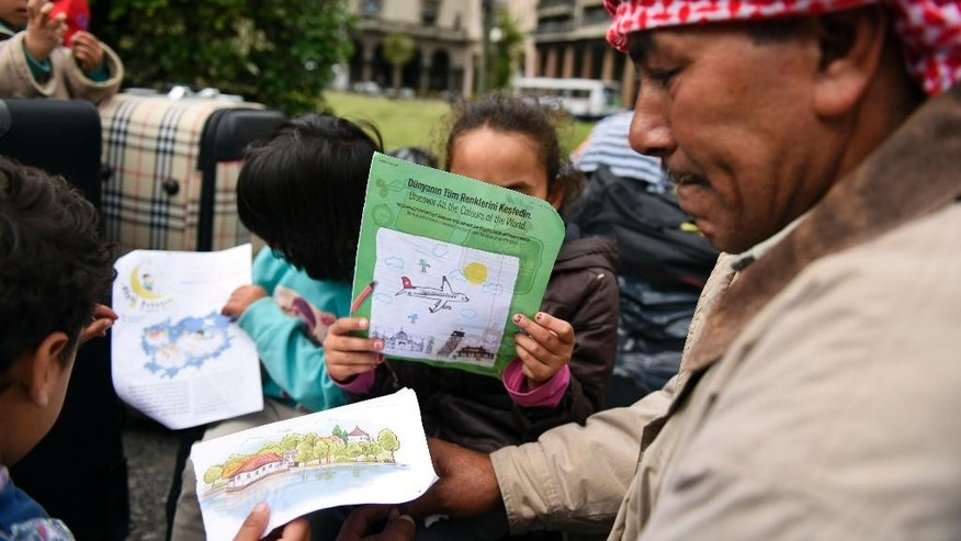 Syrian refugee children draw and read as they gather with family members at Independence Square, in Montevideo, Uruguay, Monday, Sept. 7, 2015. The group of Syrian refugees who were welcomed to Uruguay last year are staging a protest outside the government house, demanding authorities allow them to leave the South American country. They say local officials promised more than they could deliver and that Uruguay is expensive and there are no jobs. (AP Photo/Matilde Campodonico)