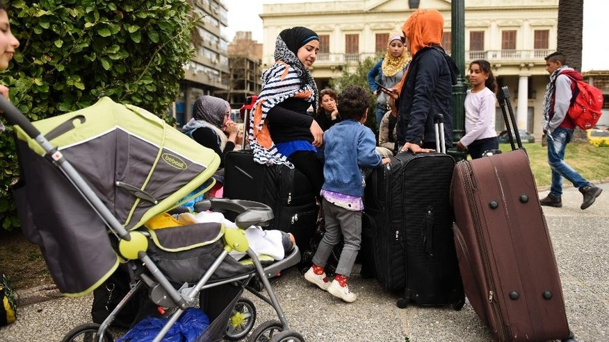 A group of Syrian refugees gather with their belongings in Independence Square in Montevideo, Uruguay, Monday, Sept. 7, 2015. The refugees who were welcomed to Uruguay last year are staging a protest demanding authorities allow them leave the South American country. Maher Aldees, the head of one family, says he wants to travel to Syria or Lebanon, and that they're going to continue the protest in front of government house until officials take them to the airport. (AP Photo/Matilde Campodonico)