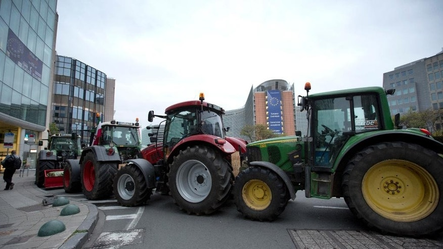 Tractors are lined up in front of EU headquarters during a farmers demonstration in Brussels on Monday, Sept. 7, 2015. European dairy farmers will demonstrate in Brussels on Monday to protest against what they believe are unfair prices on their dairy products. (AP Photo/Virginia Mayo)