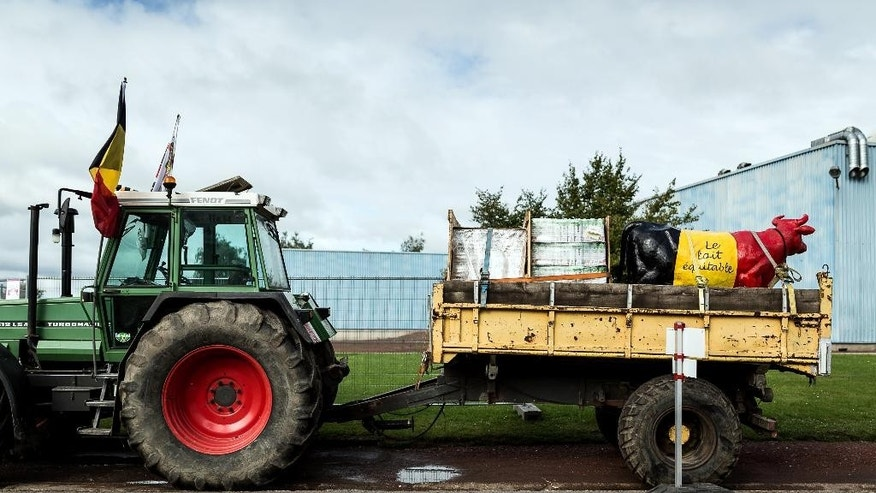 The trailer of a tractor is seen loaded with fair-trade milk and a plastic cow in front of Foire Agricole in Battice, Belgium on Sunday, Sept. 6, 2015. Farmers are expected to demonstrate in Brussels on Monday, Sept. 7, 2015 to protest what they believe is an unfair price on their dairy products. Writing on cow reads 'Fair Trade Milk'. (AP Photo/Valentin Bianchi)
