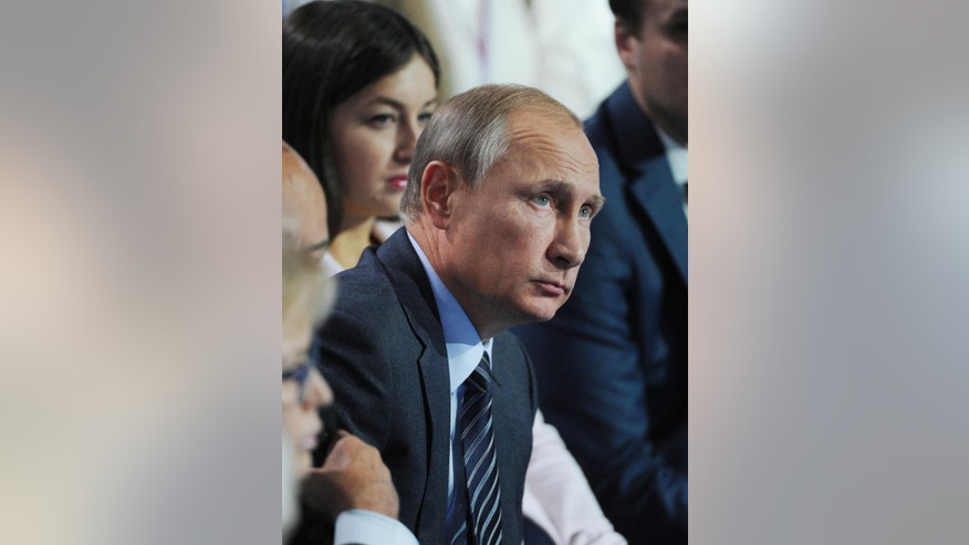 Russian President Vladimir Putin listens to a question during a meeting with supporters in Moscow, Russia, Monday, Sept.  7, 2015. Putin took part in a discussion on Monday of a health care reform with his supporters who form All-Russian People's Front. (Mikhail Klimentyev/RIA-Novosti, Kremlin Pool Photo via AP)