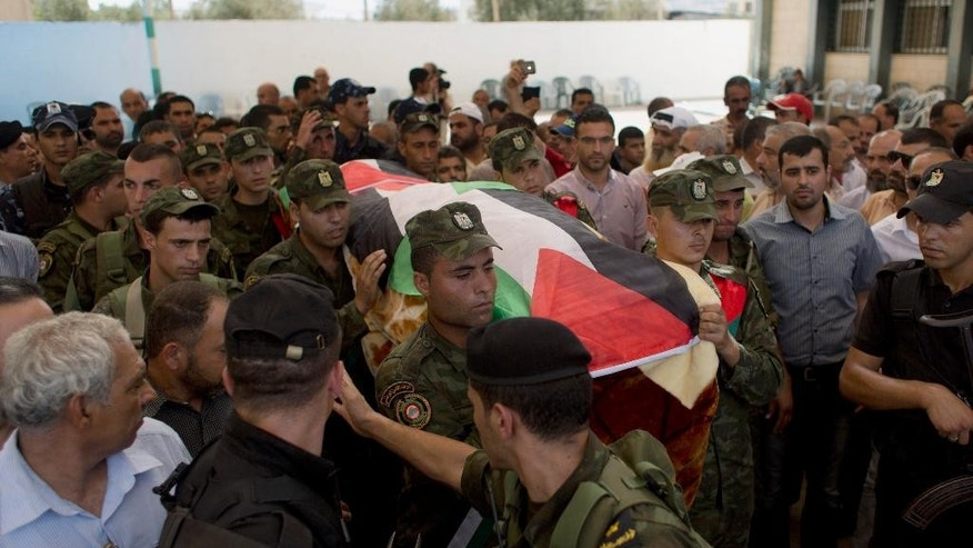 Palestinian security officers carry the body of Riham Dawabsheh, 27, during her funeral procession in the West Bank village of Duma, near Nablus, Monday, Sept. 7, 2015. The mother of a Palestinian toddler killed in a West Bank firebomb attack was buried in her village Monday hours after succumbing to wounds sustained in the attack, which also killed the child's father and is believed to have been carried out by Jewish extremists. (AP Photo/Nasser Nasser)