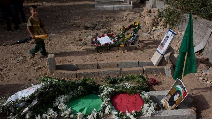 A Palestinian boy walks by the graves of Riham Dawabsheh, 27, front, her husband Saed Dawabsheh, center, and her 18-month-old son Ali, following her funeral procession in the West Bank village of Duma, near Nablus, Monday, Sept. 7, 2015. The mother of a Palestinian toddler killed in a West Bank firebomb attack was buried in her village Monday hours after succumbing to wounds sustained in the attack, which also killed the child's father and is believed to have been carried out by Jewish extremists. (AP Photo/Nasser Nasser)