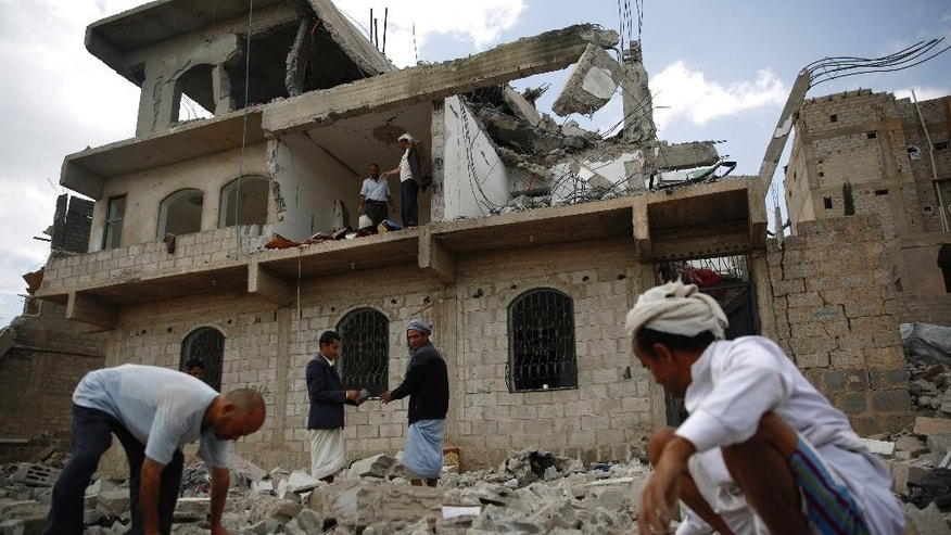People inspect on the rubble of a house damaged by a Saudi-led airstrike in Sanaa, Yemen, Monday, Sept. 7, 2015. (AP Photo/Hani Mohammed)