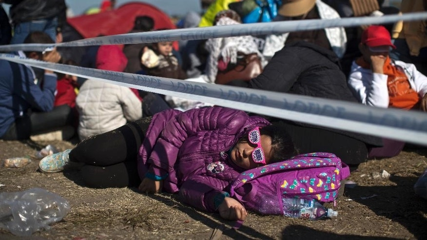 "A girl wears sunglasses that read ""Justin Bieber"" as she sleeps in a temporary holding camp close to the Hungarian border with Serbia in Roszke, Hungary, Tuesday, Sept. 8, 2015.  Hungary's Prime Minister Viktor Orban says he wants to speed up construction of a fence meant to stop migrants on the southern border with Serbia, a project which has missed two previous deadlines. (AP Photo/Marko Drobnjakovic)"