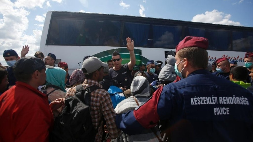Hungarian police officers stop a group of migrants before a bus that would take the migrants in Roszke, southern Hungary, Tuesday, Sept. 8, 2015. Hungarian police stood by as thousands of migrants boarded cross-border trains Sunday into Austria, taking advantage of Hungary's surprise decision to stop screening international train travelers for travel visas, a get-tough measure that the country had launched only days before to block their path to asylum in Western Europe. (AP Photo/Darko Vojinovic)