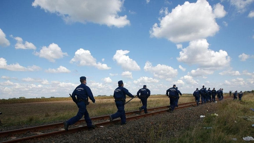Hungarian police officers run to stop a group of people at a temporary holding center for asylum seekers in Roszke, southern Hungary, Tuesday, Sept. 8, 2015. Hungarian police stood by as thousands of migrants hopped cross-border trains Sunday into Austria, taking advantage of Hungary's surprise decision to stop screening international train travelers for travel visas, a get-tough measure that the country had launched only days before to block their path to asylum in Western Europe. (AP Photo/Darko Vojinovic)