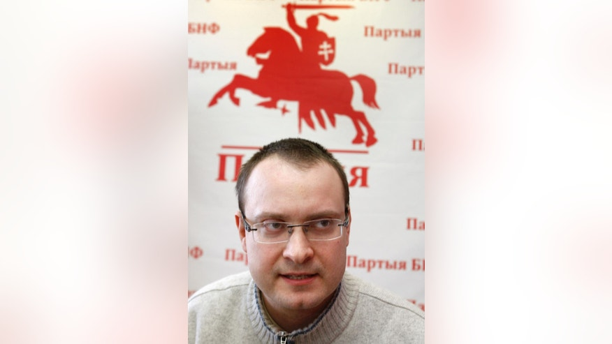 FILE - In this file photo taken on Monday, Feb. 28, 2011, Ales Mikhalevich, a candidate in Belarus' 2010 presidential election, is seen with banned national emblem behind in Minsk, Belarus.   Mikhalevich was arrested after the election and later gained political asylum in Czech Republic, and has now, Tuesday Sept. 8, 2015, been arrested while returning to Belarus after four years in exile. (AP Photo/Sergei Grits, FILE)