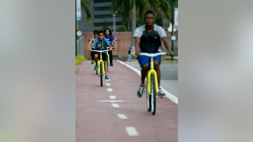In this Sept. 4, 2015 photo, people ride public bicycles on a bike path in Caracas, Venezuela. Caracas Mayor Jorge Rodriguez's seemingly-futile bet on the bike has elicited so much praise. Part of an ongoing effort to reclaim blighted public spaces, the socialist mayor inaugurated last month the final stretch of an elevated bike path, complete with Venezuela's first suspension bridge exclusively for cyclists and a giant monument in the shape of a wheel. (AP Photo/Ariana Cubillos)