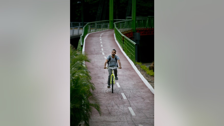 In this Sept. 4, 2015 photo, a man rides down a public bike path on Venezuela's first suspension bridge exclusively for cyclists in Caracas, Venezuela. Despite the bike program's shortcomings, it has stirred a sense of civic pride, something in short supply among Venezuelans beset by long lines for scarce foodstuffs, triple-digit inflation and one of the world's highest murder rates. (AP Photo/Ariana Cubillos)