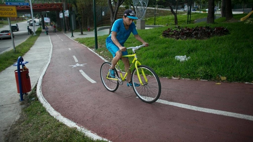 "In this Sept. 4, 2015 photo, a boy rides a public bicycle on a bike path in Caracas, Venezuela. The city launched the bike-share program lending out for free more than 100 green ""Atomic"" bikes, built in partnership with Iran. (AP Photo/Ariana Cubillos)"