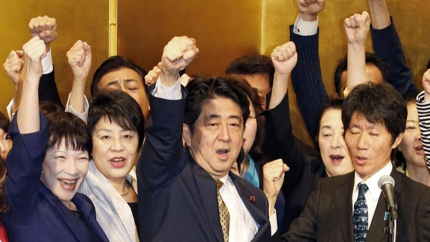 Japanese Prime Minister Shinzo Abe, center, raises his clenched fist during a kickoff rally for an election, at a hotel in Tokyo Tuesday, Sept. 8, 2015. Abe has won a new term as president of the ruling Liberal Democratic Party after facing no opposition for the job. The party named Abe president after no other lawmakers filed applications to run against him in an election that had been set for Sept. 20. (Kyodo News via AP) JAPAN OUT, MANDATORY CREDIT