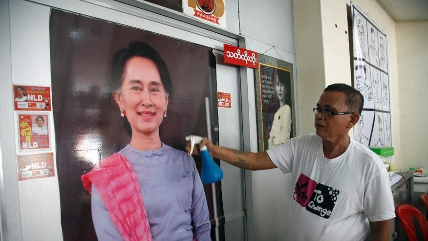 A supporter cleans a portrait of Myanmar opposition leader Aung San Suu Kyi at her National League for Democracy party headquarters in Yangon, Myanmar, Tuesday, Sept. 8, 2015. On Tuesday, the opposition leader kicked off campaigning for Myanmar's historic Nov. 8 general election with a Facebook post — one of many signs of how far the country and its most recognizable politician have come in a few years. (AP Photo/Khin Maung Win)