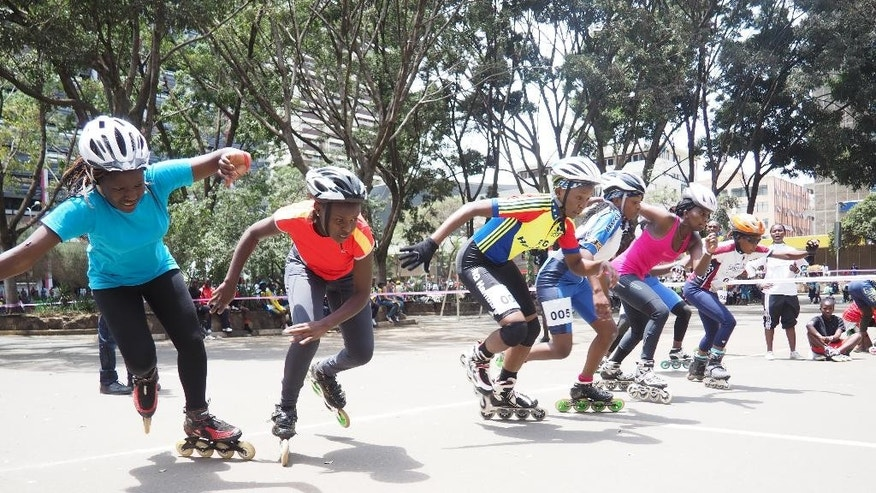 In this photo taken on Sunday, Sept. 6, 2015, Kenyan women skaters burst into action at the start of a 1000-meter race in downtown Nairobi , Kenya. A craze for roller skating has hit Kenya, fueled by its growing middle class and a love for speed. Lameck Wafula is the secretary-general of the Kenyan Federation of Roller Skating, which was created in 1997 with four members and now oversees 60 skating clubs. More than 100 schools feature roller skating at gym. A speed-skating tournament in June drew more than 400 participants from all over Kenya with hundreds more watching. A music video by Kenyan hip hop artist Octopizzo features skating. Even the police department sponsors a skating team.  (AP Photo/Jay Lawrence)