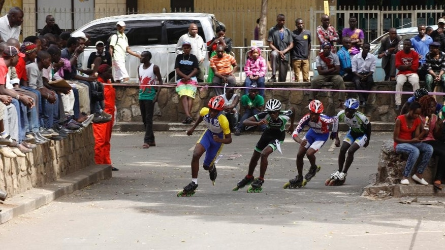 In this photo taken on Sunday, Sept. 6, 2015, Kenyan skaters burst into action at the start of a 3000-meter race in downtown Nairobi , Kenya. A craze for roller skating has hit Kenya, fueled by its growing middle class and a love for speed. Lameck Wafula is the secretary-general of the Kenyan Federation of Roller Skating, which was created in 1997 with four members and now oversees 60 skating clubs. More than 100 schools feature roller skating at gym. A speed-skating tournament in June drew more than 400 participants from all over Kenya with hundreds more watching. A music video by Kenyan hip hop artist Octopizzo features skating. Even the police department sponsors a skating team.  (AP Photo/Jay Lawrence)