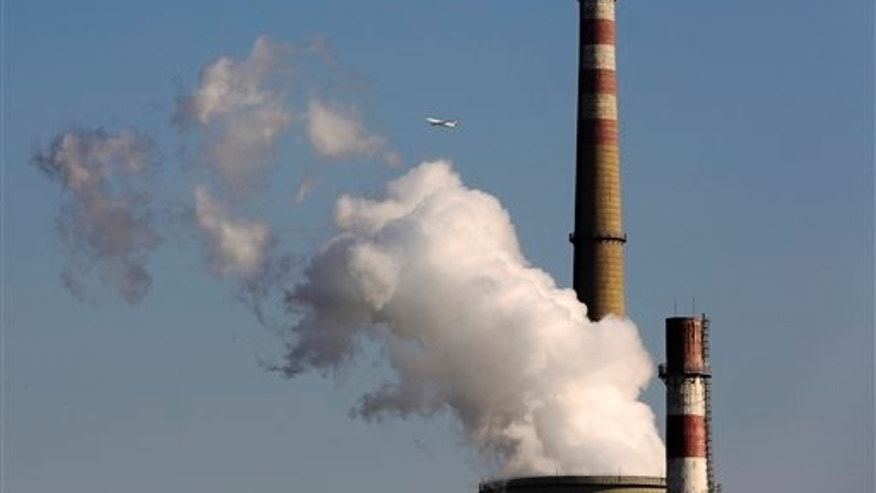 In this Nov. 13, 2014, photo, a passenger airliner flies past a coal-fired power plant in Beijing, China. U.N. climate talks are plodding ahead toward a worldwide deal to fight global warming. (AP Photo/Andy Wong, File)