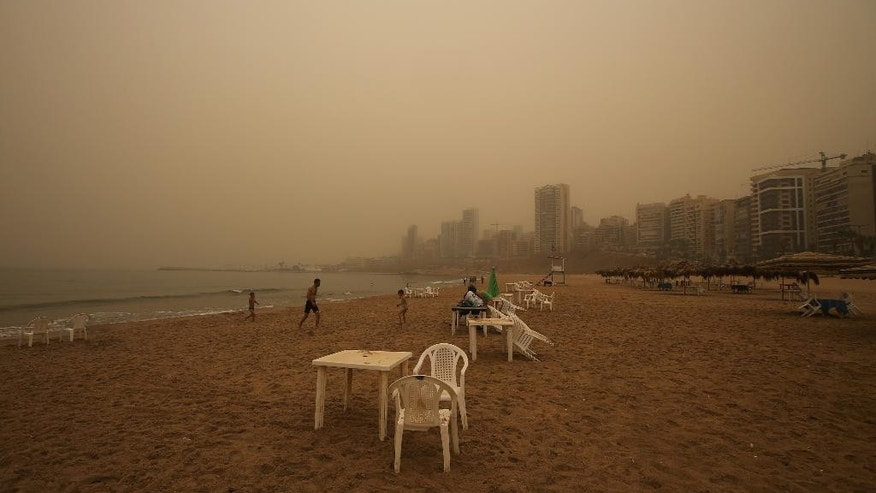 A Lebanese family walks on a popular beach as a sandstorm shrouds the coastal capital of Beirut, Lebanon, Tuesday, Sept. 8, 2015. The unseasonal sandstorm hit Lebanon and Syria, reducing visibility and sending dozens to hospitals with breathing difficulties because of the fine dust. (AP Photo/Hussein Malla)