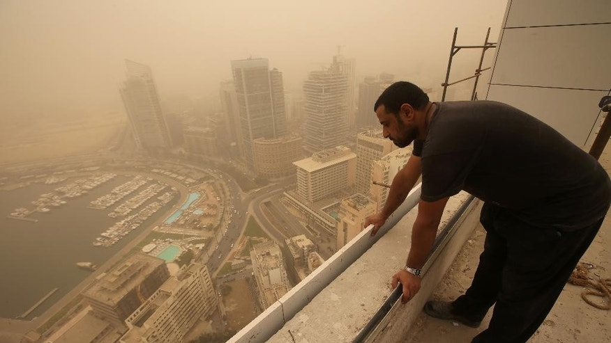 A Syrian worker  looks down from the rooftop of a high-rise tower under construction, as a sandstorm shrouds the coastal capital of Beirut, Lebanon, Tuesday, Sept. 8, 2015. The unseasonal sandstorm hit Lebanon and Syria, reducing visibility and sending dozens to hospitals with breathing difficulties because of the fine dust. (AP Photo/Hussein Malla)