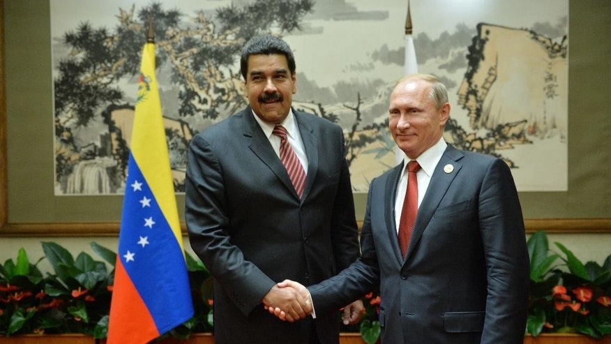 Russian President Vladimir Putin, right, shake hands with Venezuelan President Nicolas Maduro after a parade commemorating the 70th anniversary of Japan's surrender during World War II, in Beijing, Thursday, Sept. 3, 2015. (Alexei Druzhinin/RIA Novosti, Kremlin Pool Photo via AP)