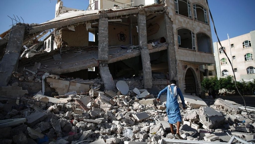 A man, walks amid the rubble of a house destroyed by a Saudi-led airstrike in Sanaa, Yemen, Tuesday, Sept. 8, 2015. (AP Photo/Hani Mohammed)
