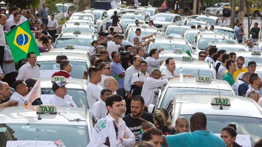 Taxi drivers block a street to protest the Uber ride-sharing service outside city council headquarters in downtown Sao Paulo, Brazil, Wednesday, Sept. 9, 2015, before a second vote by the city council that would ban Uber. To prevent the expansion of Uber elsewhere in the country, some city councils in other state capitals have laws pending approval to ban the service. (AP Photo/Andre Penner)