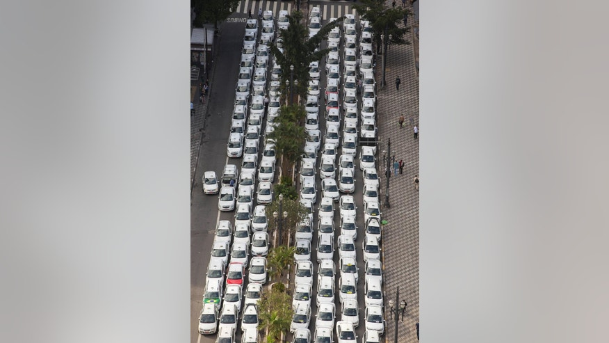 Taxi drivers block a street to protest the Uber ride-sharing service in downtown Sao Paulo, Brazil, Wednesday, Sept. 9, 2015, before a second vote by the city council on a measure that would ban Uber in the city. Cab drivers complain Uber is unfair competition because its drivers don't have to pay city fees or undergo official inspections. (AP Photo/Andre Penner)