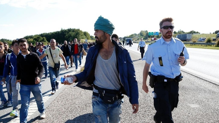 Migrants walk north on the highway in Southern Denmark, Wednesday, Sept. 9, 2015. Danish railway company DSB says all train service has been halted between Germany and Denmark after Danish police stopped hundreds of migrants arriving by train across the border. Danish police spokeswoman Anne Soe says about 100 migrants who arrived from Germany on Wednesday are refusing to leave a train in the Danish port city of Roedby. Many of the migrants say they want to go to Sweden, Norway or Finland, because they have relatives there or believe that the conditions for asylum-seekers are better. (Martin Lehmann/Polfoto via AP)      DENMARK OUT