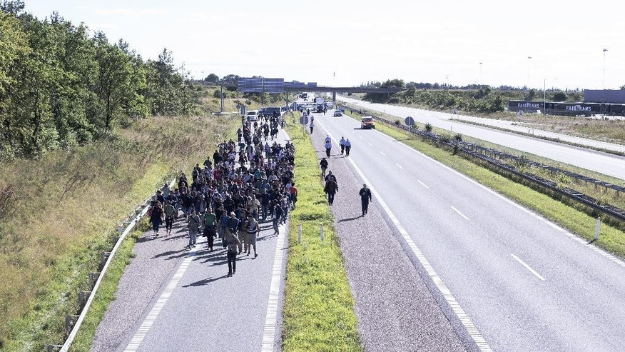 Around 300 migrants walk north on a highway escorted by police in southern Denmark on Wednesday, Sept. 9, 2015.  The migrants have crossed the border from Germany, and after staying at a local school, they say they are now making their way to Sweden, to seek asylum.  (Rune Aarestrup Pedersen/Polfoto via AP) DENMARK OUT