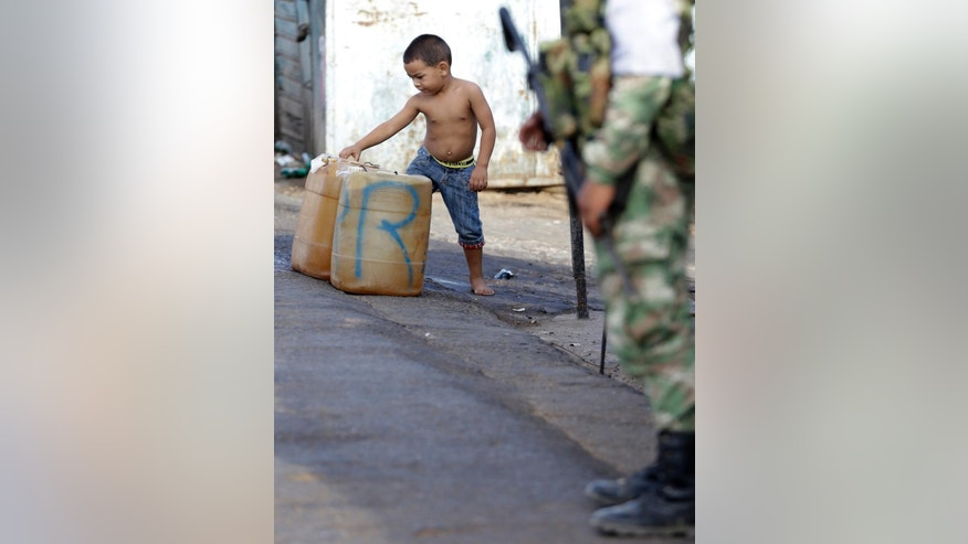 A boy checks out containers filled with gasoline, in Paraguachon, Colombia, Wednesday, Sept. 9, 2015. Venezuelan President Nicolas Maduro has expanded an anti-smuggling offensive along the country's frontier with Colombia, and ordered another main crossing, this one in Paraguachon, closed Monday night as part of a two-week-old anti-smuggling offensive. (AP Photo/Fernando Vergara)