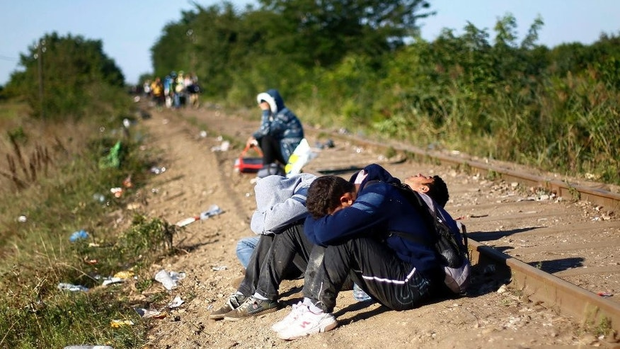 Migrants rest by the railway track near Roszke, southern Hungary, Wednesday, Sept. 9, 2015. Migrants anxious to pass through Hungary towards central Europe are making their way on foot at Hungary's southern border with Serbia. (AP Photo/Matthias Schrader)