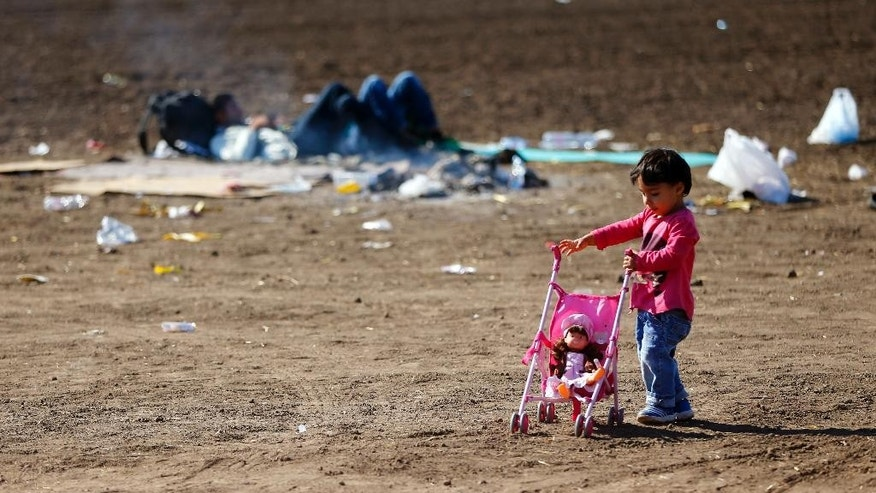 A young girl plays with a doll on a field while waiting in a camp near the border line between Serbia and Hungary in Roszke, southern Hungary, Wednesday, Sept. 9, 2015. Migrants anxious to pass through Hungary towards central Europe are making their way on foot at Hungary's southern border with Serbia. (AP Photo/Matthias Schrader)