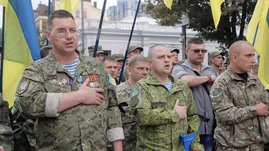 Ukrainian servicemen, wounded in battles in the country's east, sing the Ukrainian national anthem during commemoration ceremony for three officers killed in a terrorist act on Aug. 31, in front of the parliament building in Kiev, Ukraine, Wednesday, Sept. 9, 2015. Police said 141 people had been wounded in a terrorist act as a nationalist protest in Kiev turned violent, with 10 of the injured in serious condition.  (AP Photo/Efrem Lukatsky)