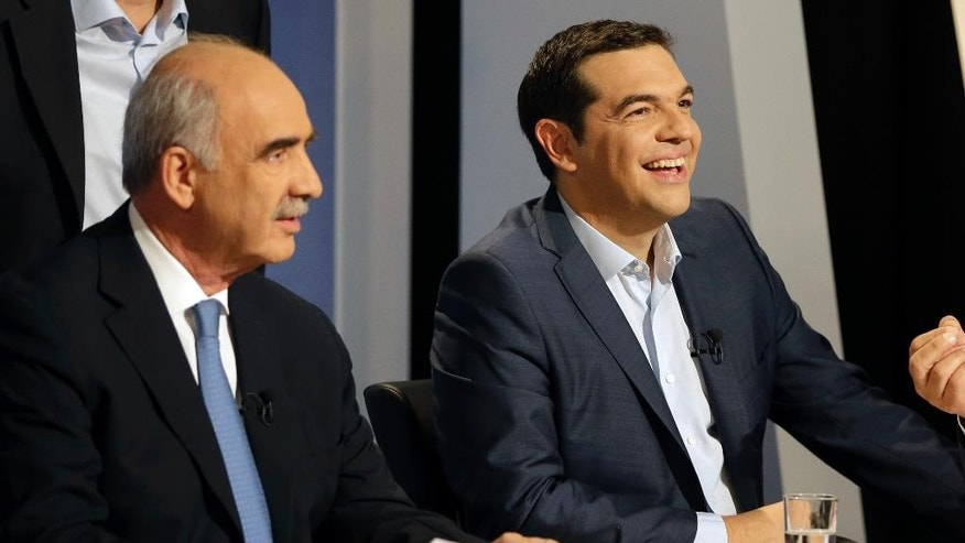The leader of the left-wing Syriza party and former Greek Prime Minister Alexis Tsipras laughs as main opposition conservative New Democracy head Vangelis Meimarakis waits for the start of a live televised debate at the state-run ERT television in Athens, Wednesday, Sept. 9, 2015. The leaders of all but one of Greece's main political parties hold a live televised debate for the first time in six years on Wednesday night before the country's Sept. 20 early election. (AP Photo/Thanassis Stavrakis)