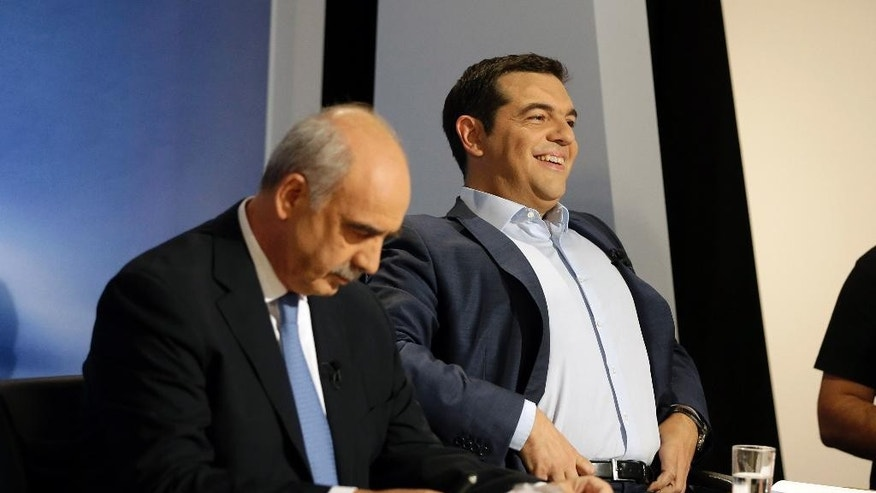 The leader of the left-wing Syriza party and former Greek Prime Minister Alexis Tsipras, right, adjusts his shirt as main opposition conservative New Democracy head Vangelis Meimarakis reads his notes before a live televised debate at the state-run ERT television in Athens, Wednesday, Sept. 9, 2015. The leaders of all but one of Greece's main political parties hold a live televised debate for the first time in six years on Wednesday night before the country's Sept. 20 early election. (AP Photo/Thanassis Stavrakis)