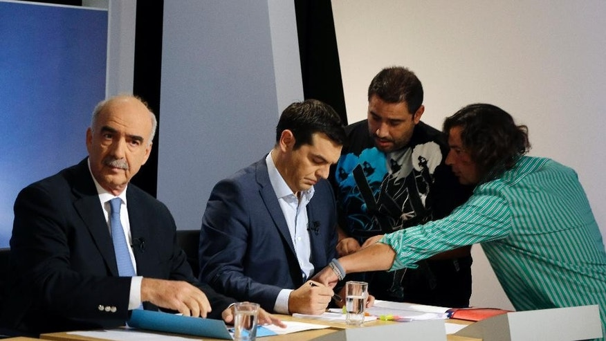 The leader of the left-wing Syriza party and former Greek Prime Minister Alexis Tsipras, right, reads his notes as technicians prepare him and main opposition conservative New Democracy head Vangelis Meimarakis before a live televised debate at the state-run ERT television in Athens, Wednesday, Sept. 9, 2015. The leaders of all but one of Greece's main political parties hold a live televised debate for the first time in six years on Wednesday night before the country's Sept. 20 early election. (AP Photo/Thanassis Stavrakis)