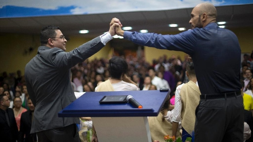 Preacher Marcos Gladstone, left, and holds the hand of his husband Fabio Inacio during a service at the Contemporary Christian Church in Rio de Janeiro, Brazil, Monday, Sept. 7, 2015.  Gladstone and his spouse are co-founders of the Contemporary Christian Church, one of a handful of Pentecostal denominations in Brazil that welcomes gays and lesbians with open arms. (AP Photo/Silvia Izquierdo)