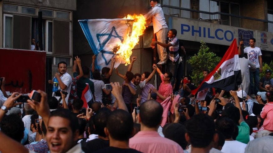 FILE - In this Friday, Sept. 9, 2011 file photo, Egyptian protesters burn a representation of the Israeli flag outside the Israeli Embassy in Cairo, Egypt, as they demolish a concrete wall built to protect the embassy from demonstrators. Israel has reopened its embassy in Cairo, four years after an Egyptian mob ransacked the site where the mission was previously located. The Israeli flag was raised during its opening ceremony at the new location of the embassy on Wednesday, Sept. 9, 2015. (AP Photo/Khalil Hamra, File)
