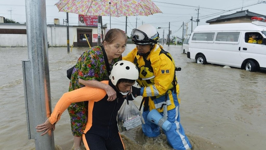 Police officers help a woman to evacuate through a flooded street in Joso, Ibaraki prefecture, northeast of Tokyo Thursday, Sept. 10, 2015. Heavy rains batter Japan for the second day, causing flooding and landslides in eastern Japan. (Kyodo News via AP) JAPAN OUT, MANDATORY CREDIT